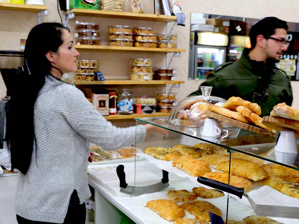 נטלי רוסין מסבירה ללקוח סקרן על המאפים הגיאורגים