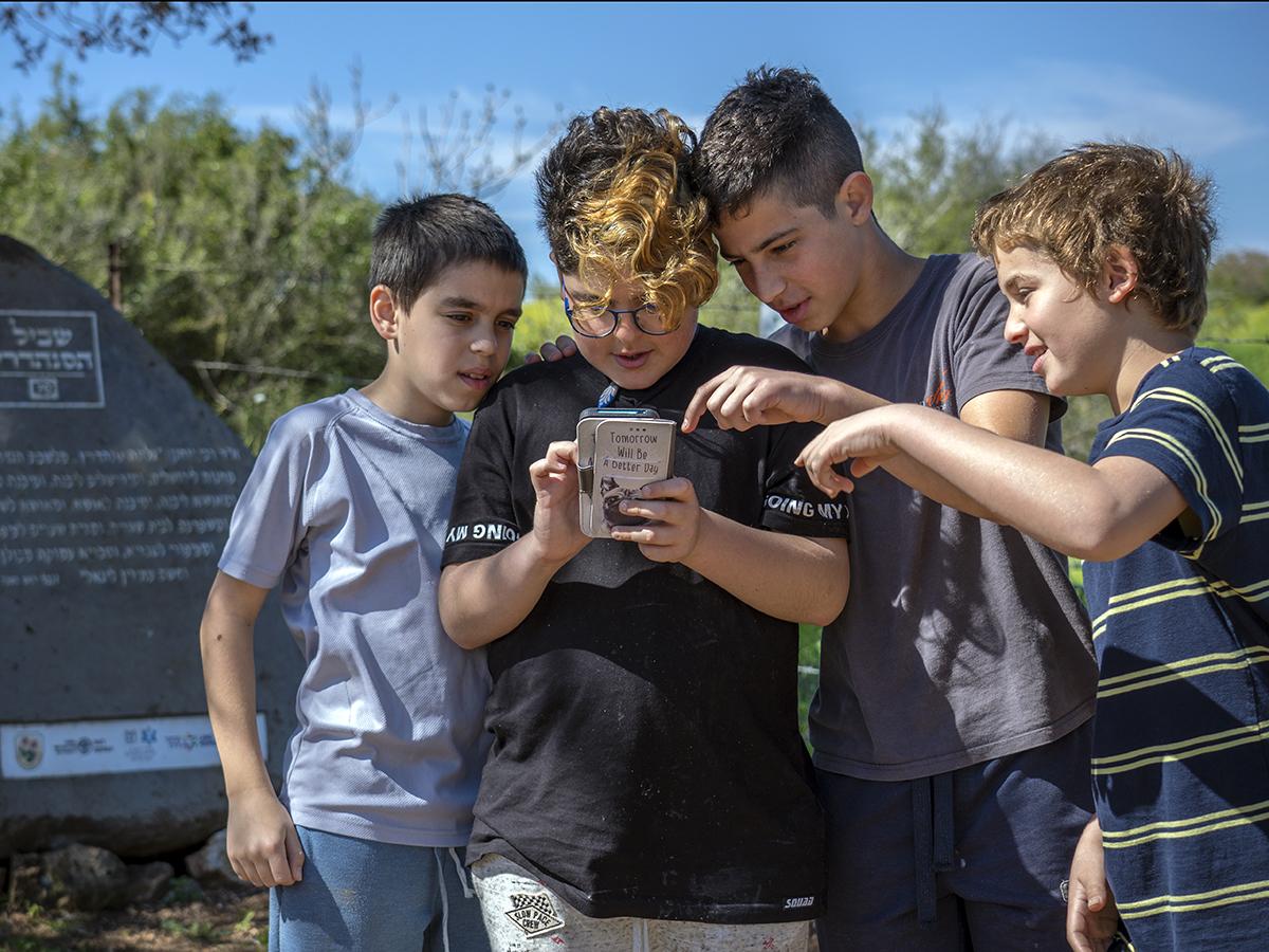 תלמידים בוחנים את אפליקצית שביל הסנהדרין לצד האבן החכמה שהוצבה לאורך המסלול. צילום יניב ברמן רשות העתיקות3.