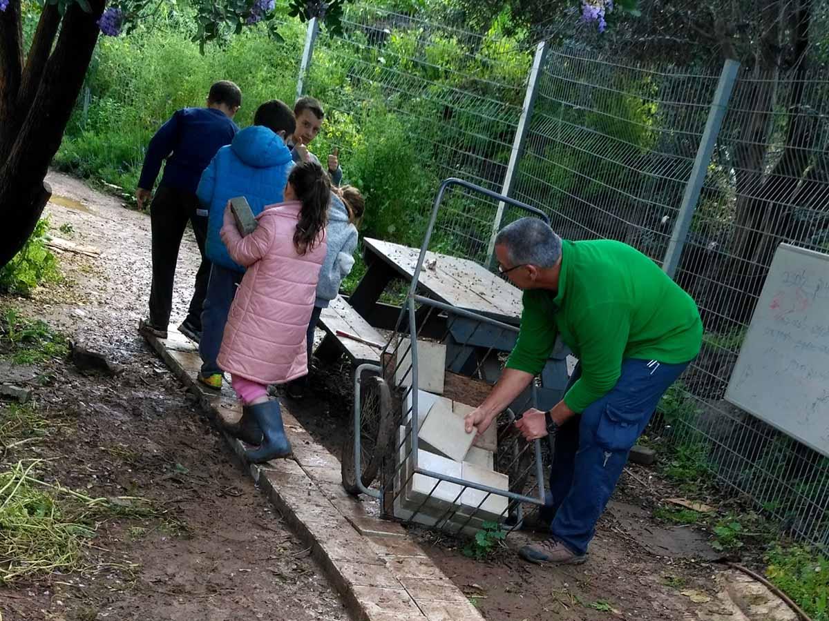 התלמידים בונים מדרכה יחד עם המנהל אורי ברזק