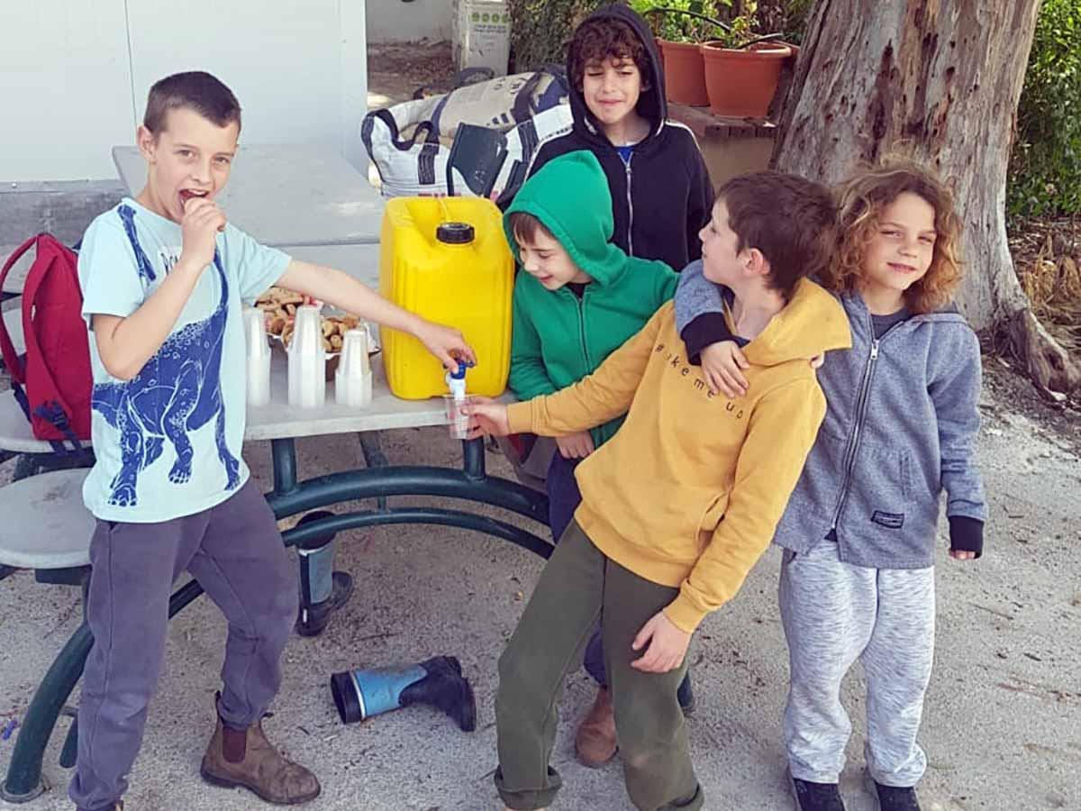 התלמידים מחלקים קפה לחברי הקיבוץ