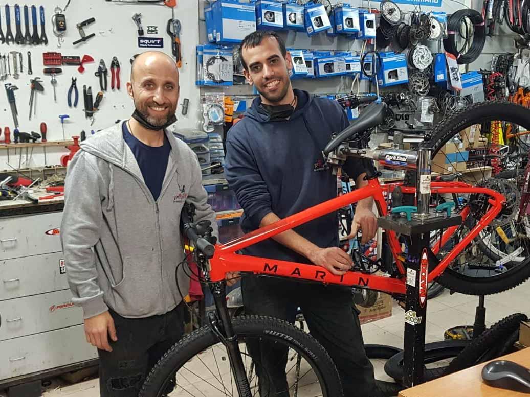 """קובי קובי שושני ורן אלופי העולם מחנות האופניים מס' 1 בעפולה אופן אופן על רקע אופני ה""""מרין"""" החדשות שנחתו בחנות."""